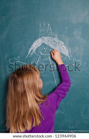 Young girl drawing an image of a princess with crown on chalkboard