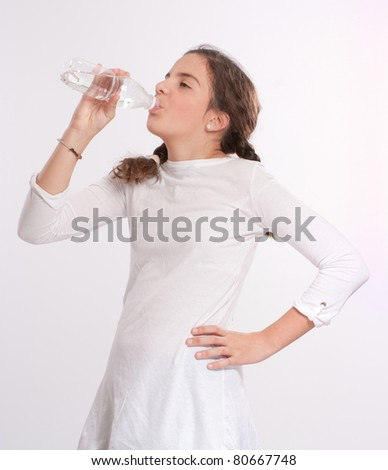 Young girl drinking water from a plastic bottle
