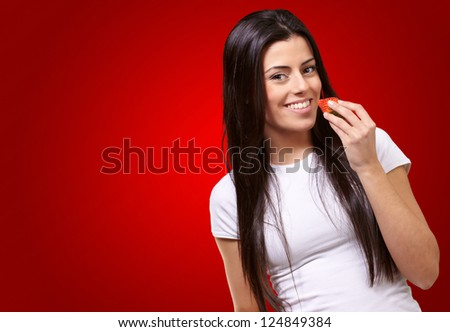 Young Girl Eating And Holding Strawberry Isolated On Red Background