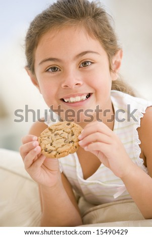 Young girl eating cookie in living room smiling