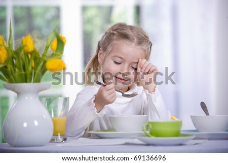 young girl eating muesli from the bowl