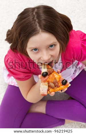 Young girl eating pizza sitting on the floor