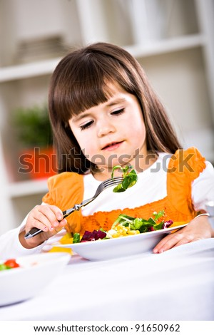 young girl eating salad at home. A studio shoot.
