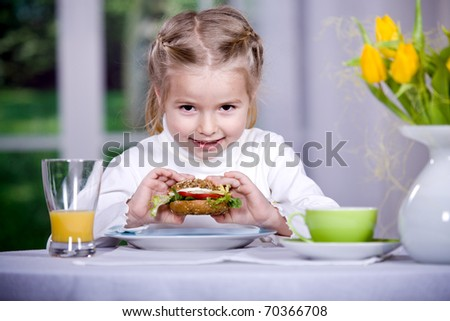 young girl eating sandwich with lettuce leaves