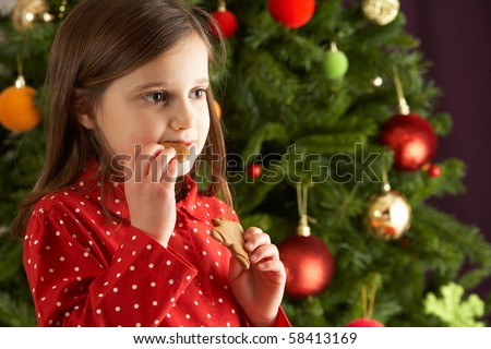 Young Girl Eating Star Shaped Christmas Cookie In Front Of Christmas Tree