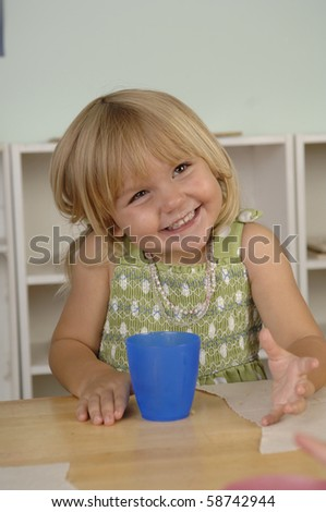 Young girl eats her snack during the break from her preschool classes.