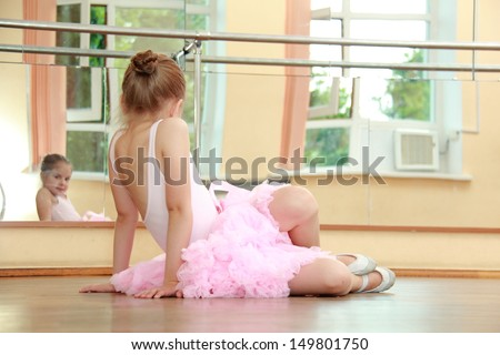 Young girl engaged in a pink ballet tutu and pointes in the ballet hall on the wooden dance floor