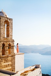 Young girl enjoying breathtaking sunset view from atop of Greek Orthodox church in Plaka village on Milos island