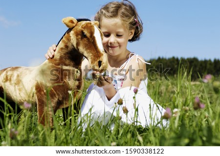 Young girl feeding stuffed animal horse in meadow