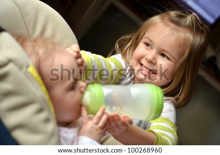 Young girl feeds her baby sister in a highchair