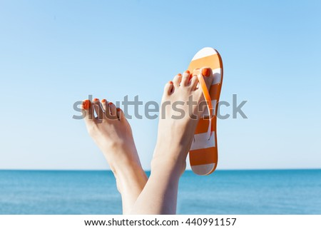Young girl feet in colorful flip-flop sandal on sea beach #440991157