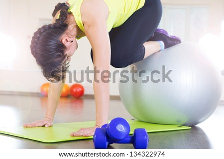 Young girl fitness workout in gym with fitball