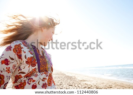 Young girl flicking her hair on a golden sand beach with the sun rays filtering through her hair while she smiles, joyful.