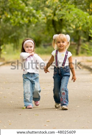 Young girl-friends go for a walk the park - stock photo