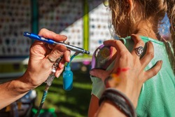 Young girl getting an airbrush stencil temporary tattoo in a family festival outdoors - Closeup picture with many different tattoo designs displayed in the blurry background