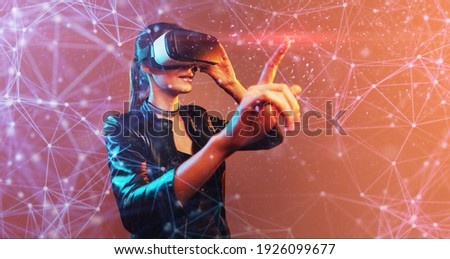 Young girl getting experience VR headset is using augmented reality eyeglasses being in virtual reality. Girl with hands up wearing virtual reality goggles. Woman touching air during VR experience