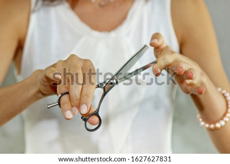 Young girl hairdresser holds scissors on outstretched hand to the viewer, standing on a gray background. The concept of creating haircuts