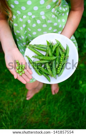 Young girl hand holding organic green natural healthy food produce green Peas