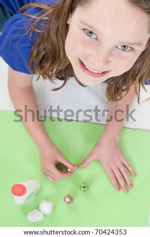 young girl happily polishing nails