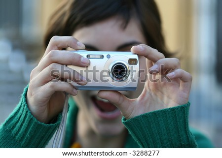 young girl has fun taking pictures with her digital camera