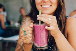 Young girl having a good morning healthy breakfast smoothie drink made of super foods, fruits, nuts, berries