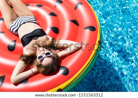 Young girl having floating with watermelon and taking sun in summer vacation. Vacation concept