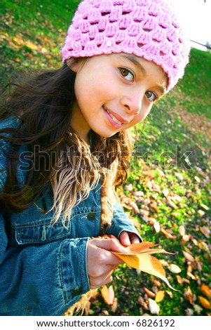 Young girl having fun collecting fallen autumn leaves in the park