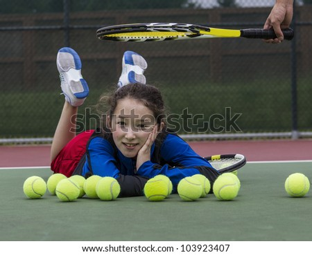 Young girl having fun on outdoor tennis courts with coach's racket above her head - stock photo