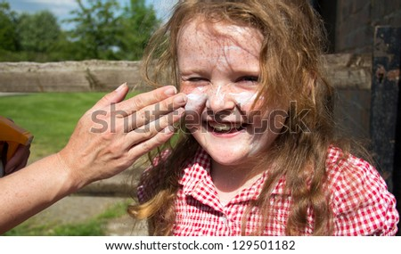 Young girl having her face covered with sun protection