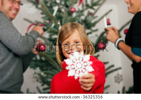 Young girl helping her family decorating the Christmas tree, holding a Christmas Snowflake in her hand