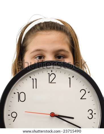 Young girl hiding behind a large wall clock, isolated against a white background