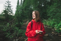 Young girl hiker in a red raincoat is smiling holding phone in her hands on a background of mountain forest. Female traveler in red jacket smiling and feeling cheerful in the fir woods near the river.