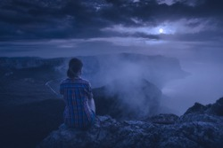 Young girl hiker sitting on a cliff and enjoy the full moon rising above the foggy mountains of Crimea. Travel concept.