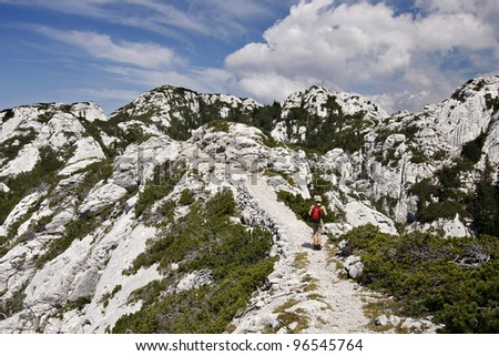 Young girl hiking on Premuzic's trail, a path around 50km through North and Middle Velebit, made of stones