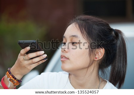 Young girl hold mobile phone in her hand with out focus background