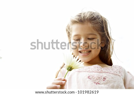 Young girl holding a daisy flower against the sky.