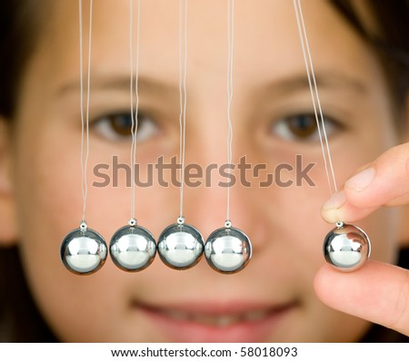 young girl holding a pendulum ball