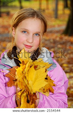 Young girl holding a pile of autumn maple leaves