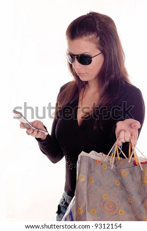 Young girl holding bags and sending message on mobile