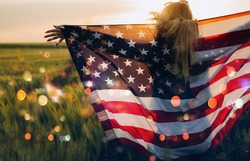 Young girl holding Bengal fire with American flag at sunset. America celebrate 4th of July. Independence Day.