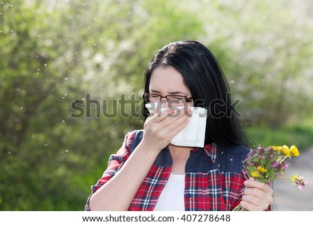 Young girl holding bouquet of wildflowers and blowing nose in tissue paper. Allergies concept