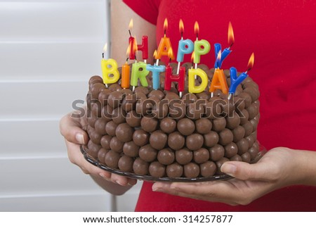Young girl holding Chocolate Birthday Cake decorated with candy malt balls in front of her with happy birthday candles burning. Fast and easy home made cake for children or adult birthday party