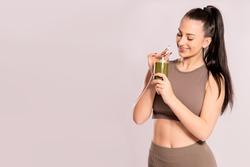 Young girl holding green smoothie standing on light grey background with copy space. Concept of fitness and detox