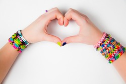 Young girl holding hands in a heart shape, wearing loom bracelets. Close up. Young fashion concept