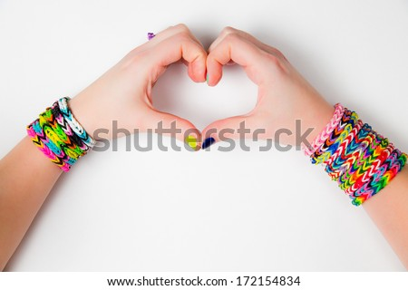 Young girl holding hands in a heart shape wearing loom bracelets Close up Young fashion concept