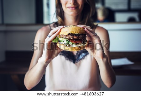 Young girl holding in female hands fast food burger, american unhealthy calories meal on background, mockup space for text message or design, hungry person smiling with grilled hamburger front view