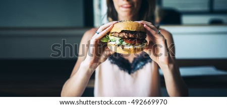 Young girl holding in female hands fast food burger, american unhealthy calories meal on background, mockup with copy space for text message or design, hungry human with grilled hamburger front view