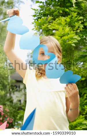 Young girl holding paper heart cut-outs