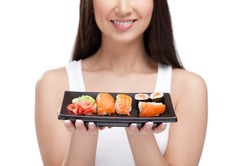 Young girl holding plate of sushi in her hands and smiling