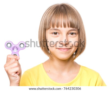 Young girl holding popular fidget spinner toy - close up portrait. Happy smiling child playing with Spinner, isolated on white background. #764230306